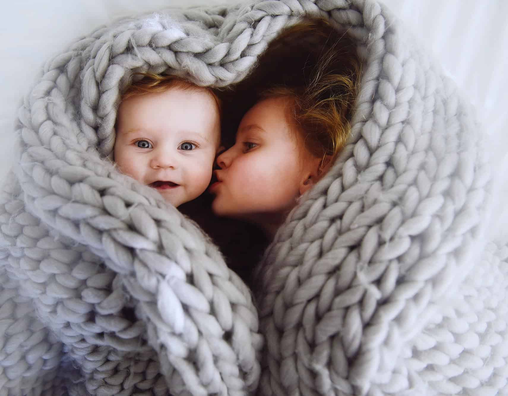 A sister kissing her baby brother while wrapped up in a blanket