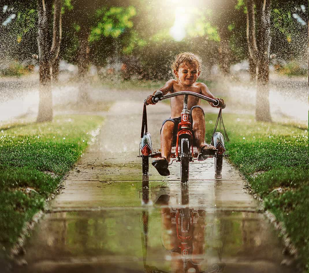 A young boy racing his trike on a pavement through water sprinklers