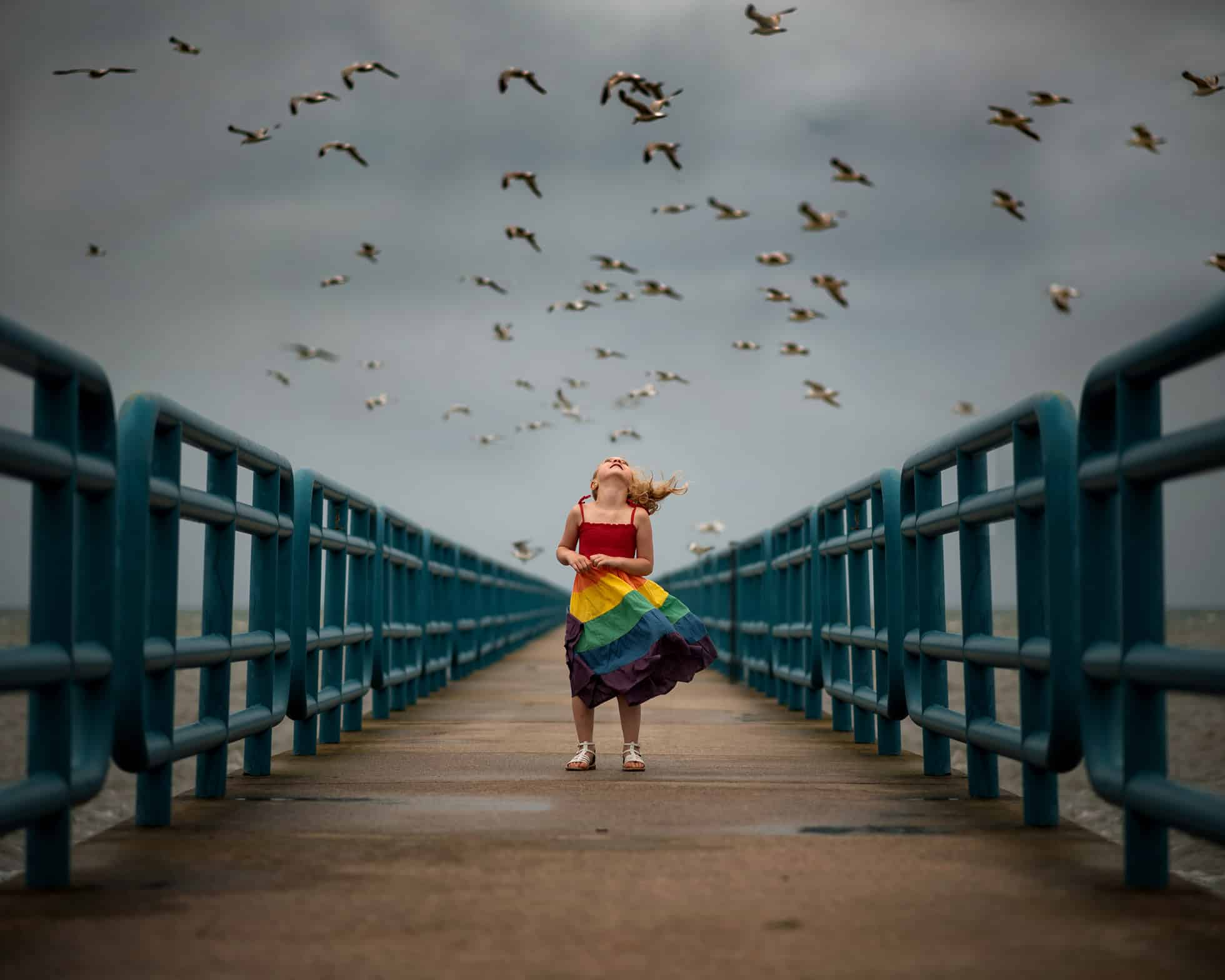 A small girl standing in the middle of a bridge with a bunch of birds above her
