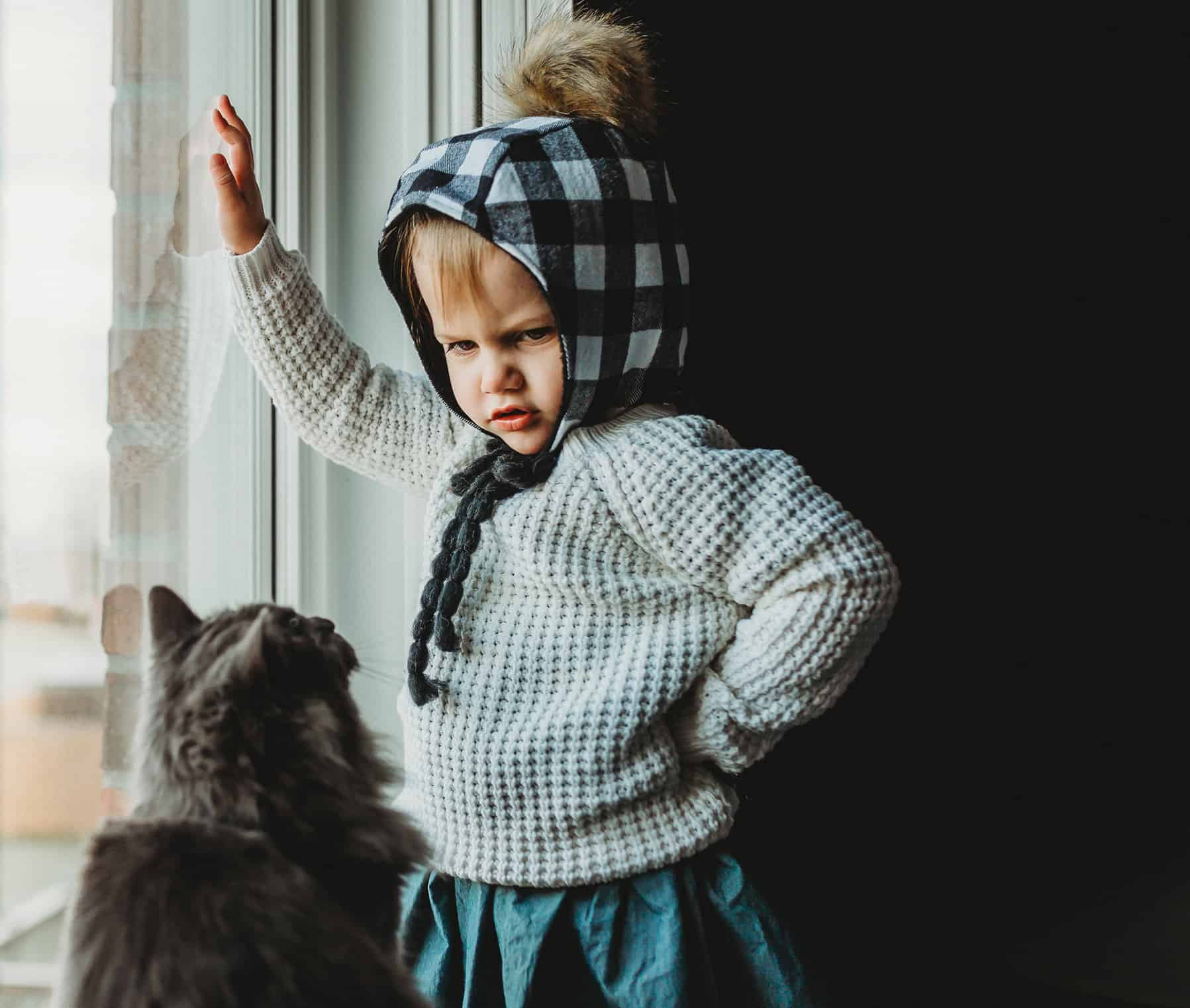 A small girl looking at her cat in a funny way while having her hand lean up to the window