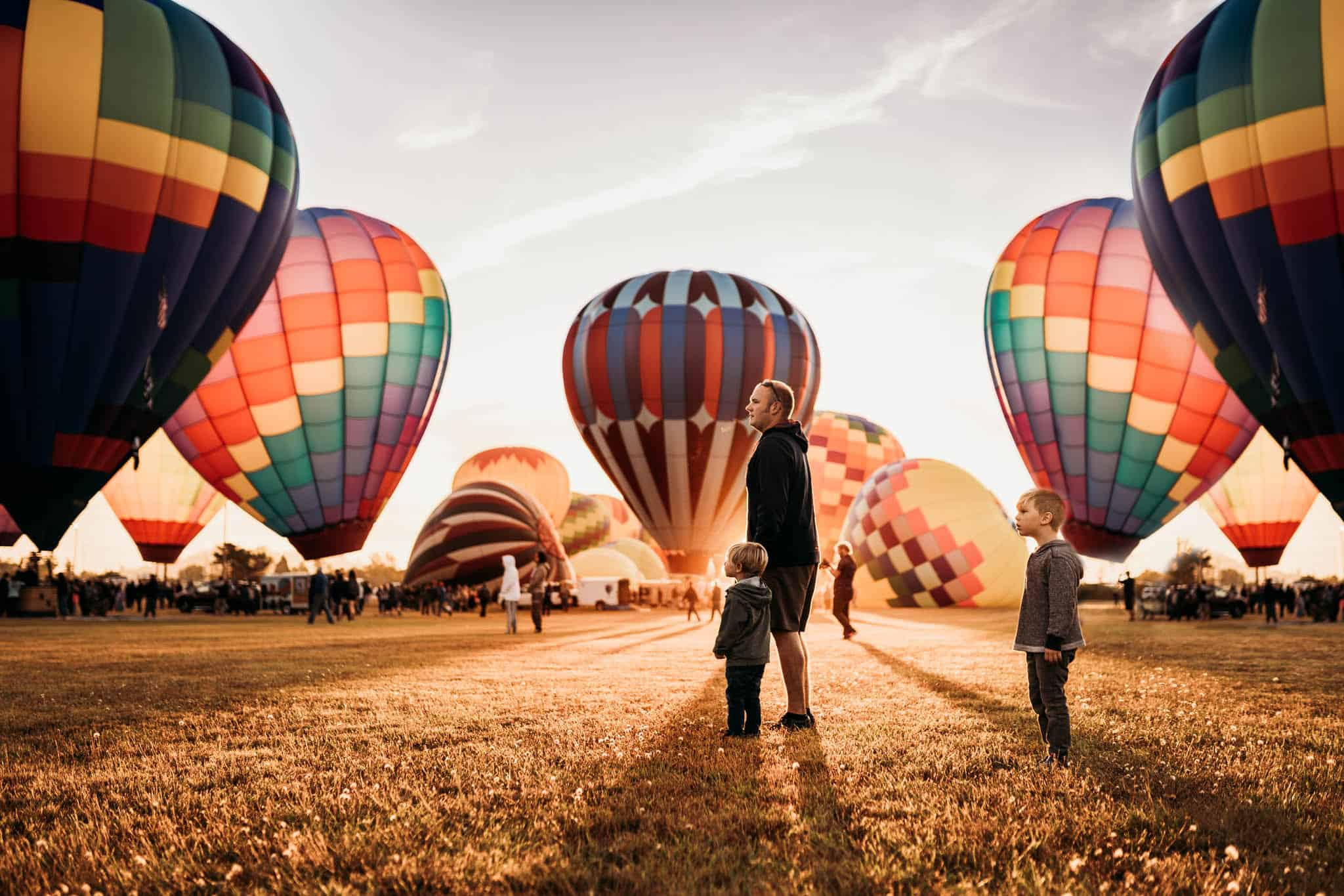 A father and his two sons are standing in the middle of a hot air ballon starting point