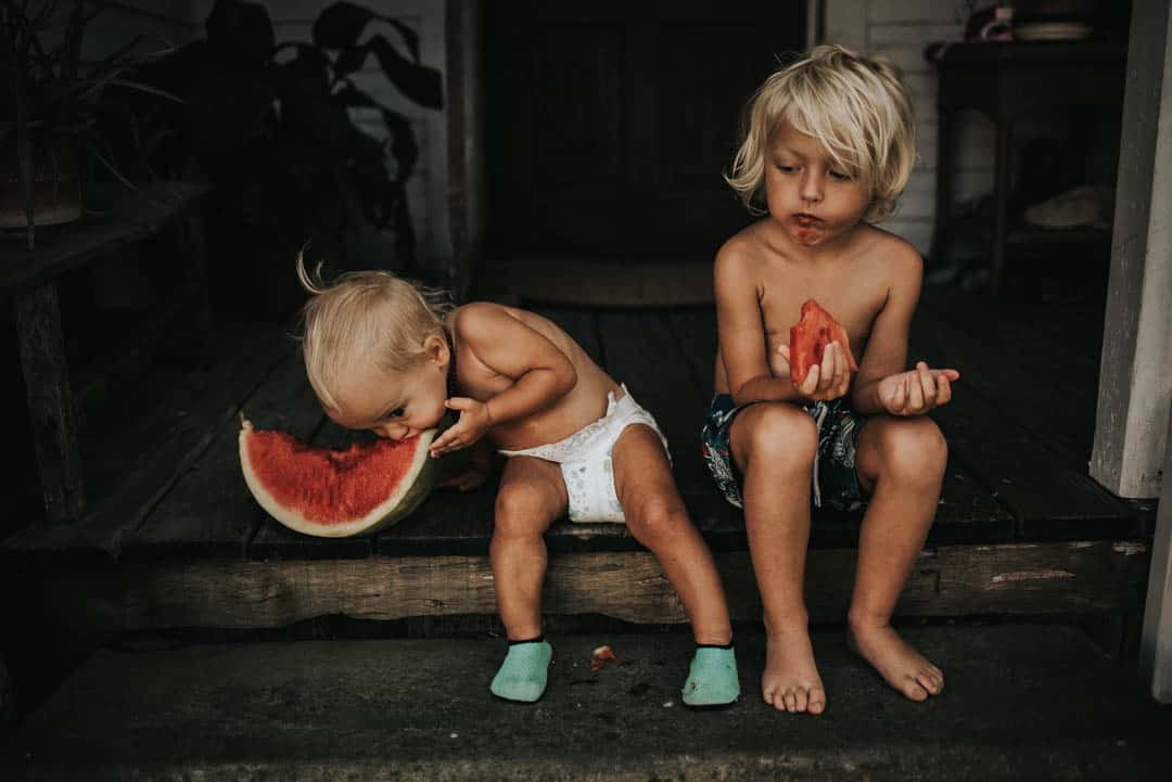 Two small kids eating a watermelon sitting on their front porch