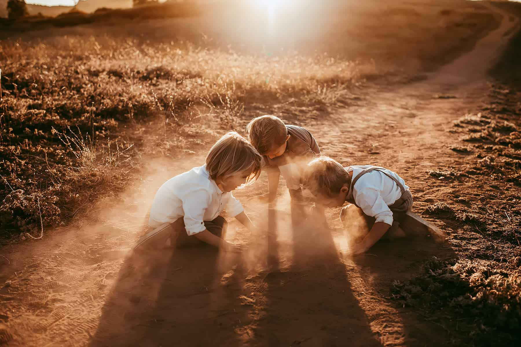 A small group of kids playing on a dirt road while the dust is lit up by the setting sun