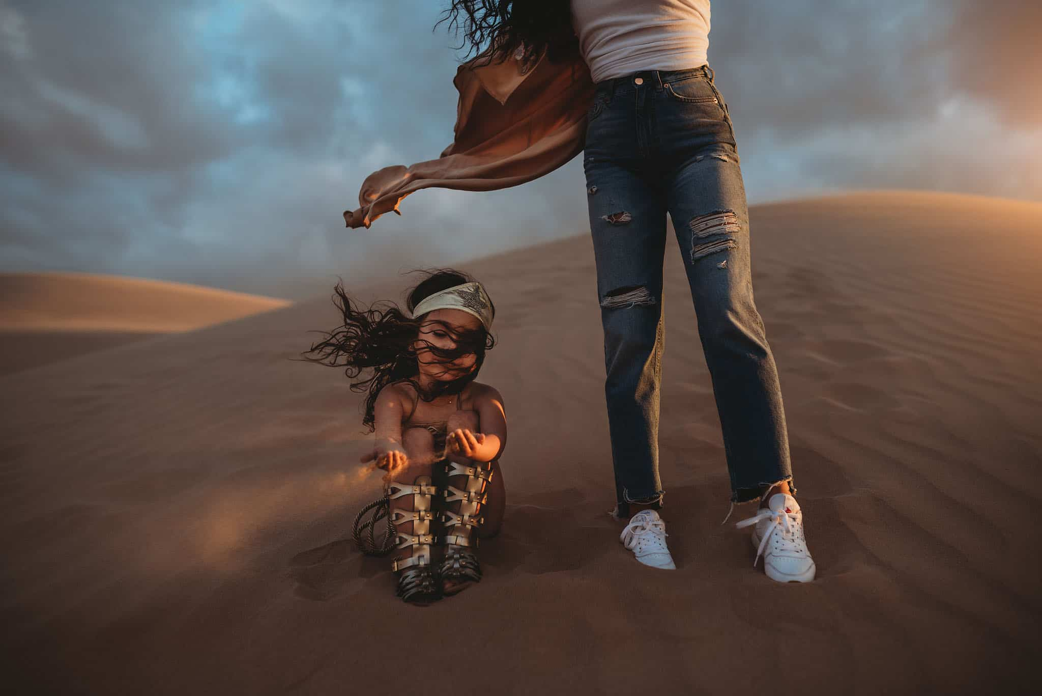 A small girl sitting on sand dunes next to her mother playing with sand