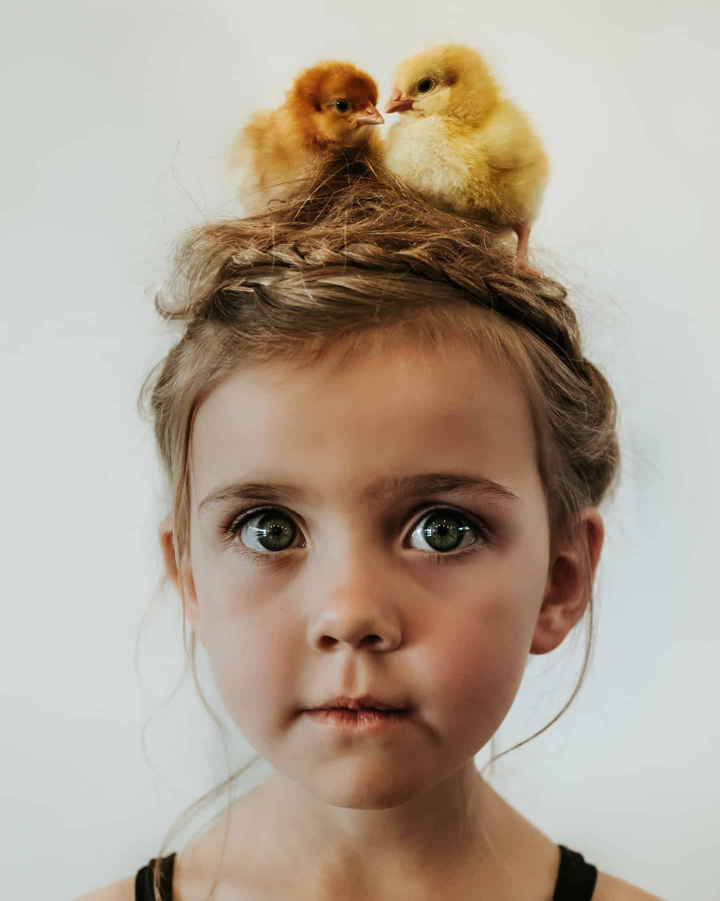 A portrait of a young girl with two ducklings on her head