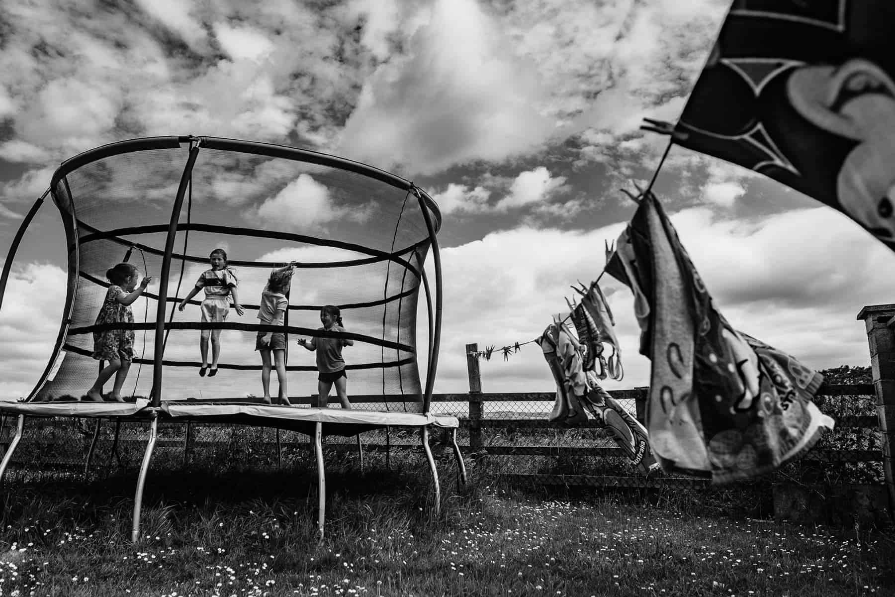 4 kids jumping on a trampoline with clouds behind them