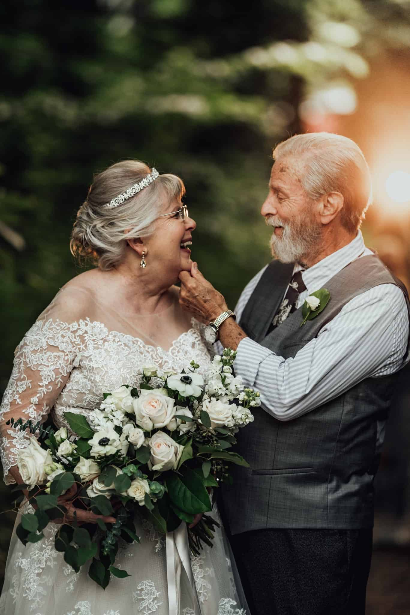 Elderly couple smiling at each other on their wedding day