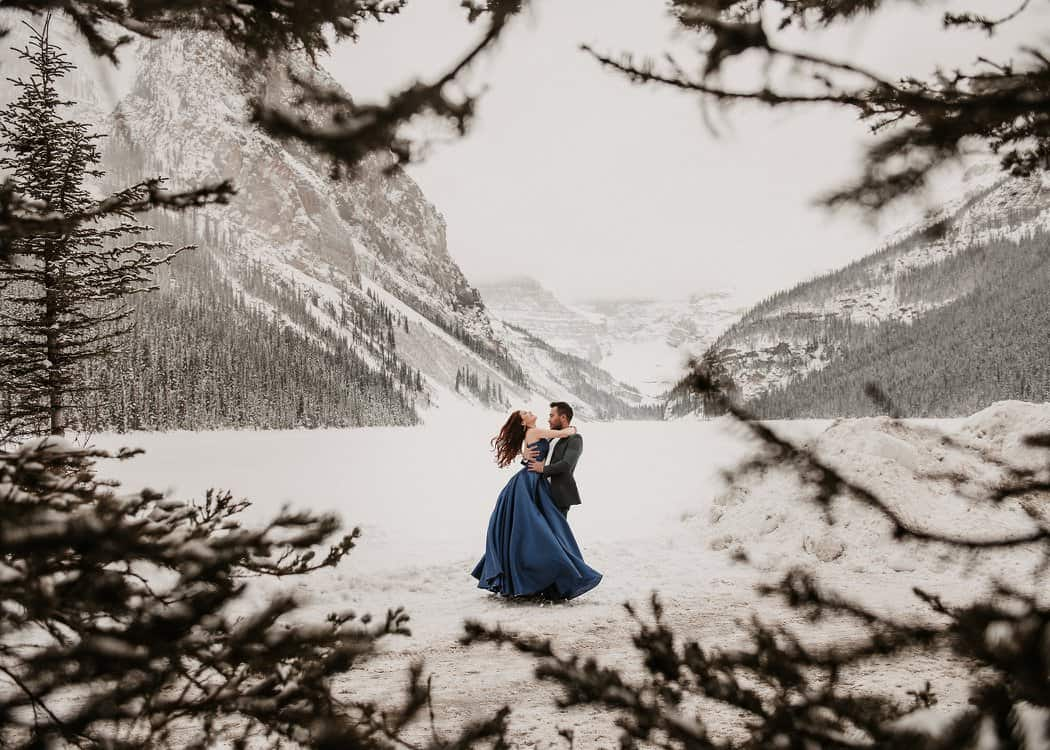A wedding couple dancing o a snowy field