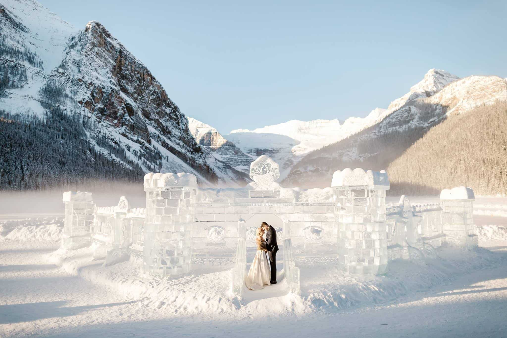 A wedding couple standing in front of a castle made of ice