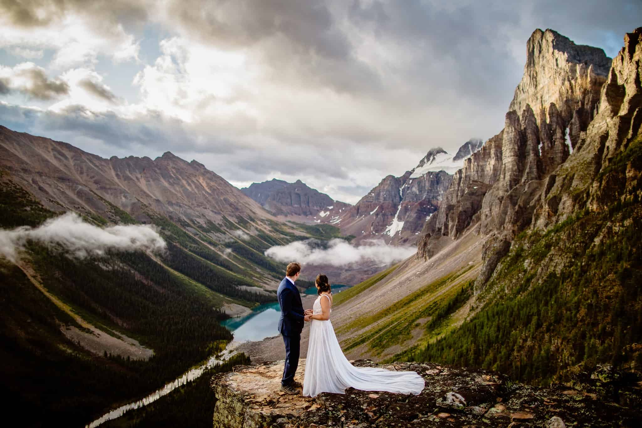 A wedding couple looking down on Banff national park in Canada
