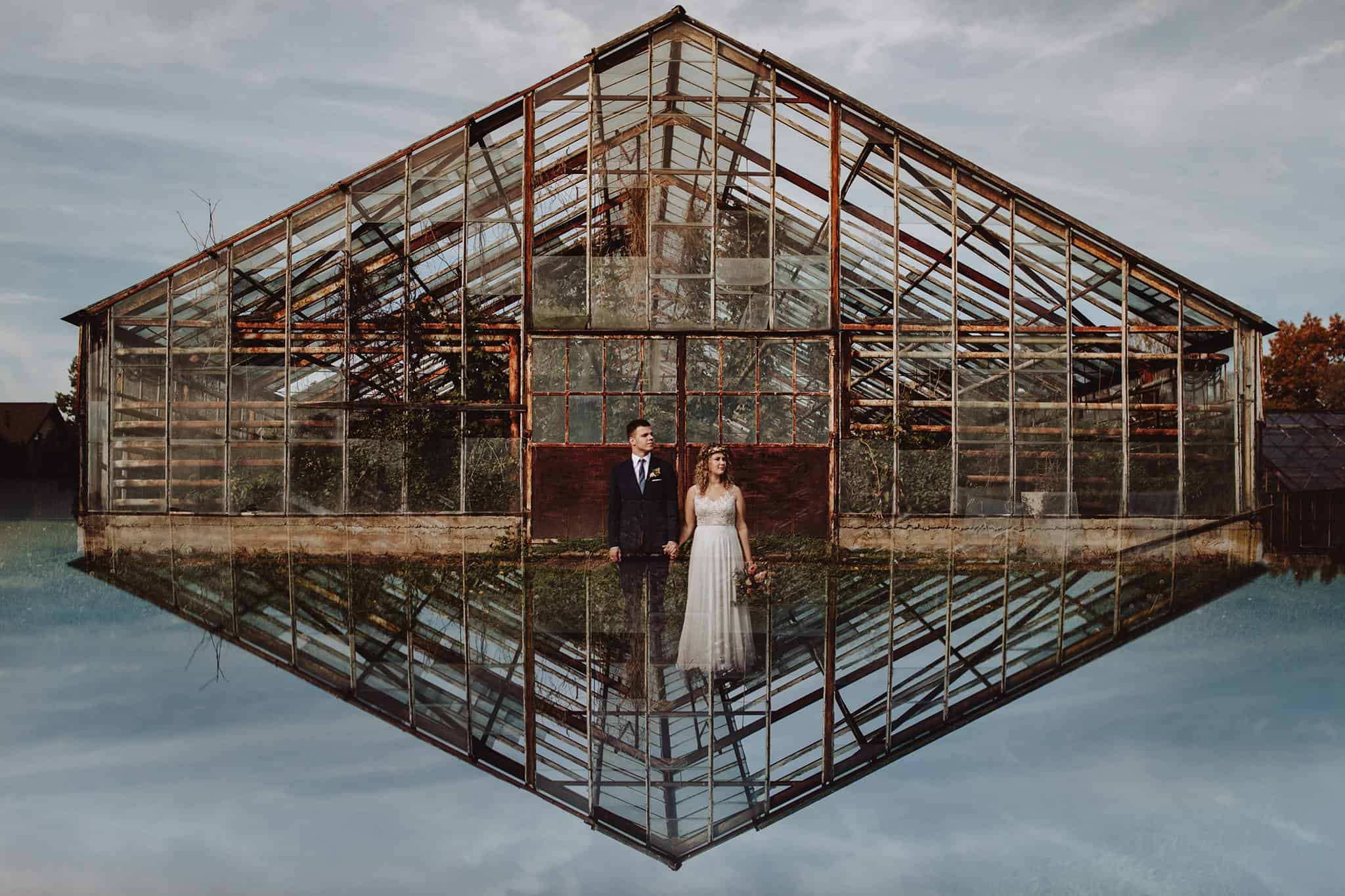 A couple standing in front of a greenhouse on their wedding day