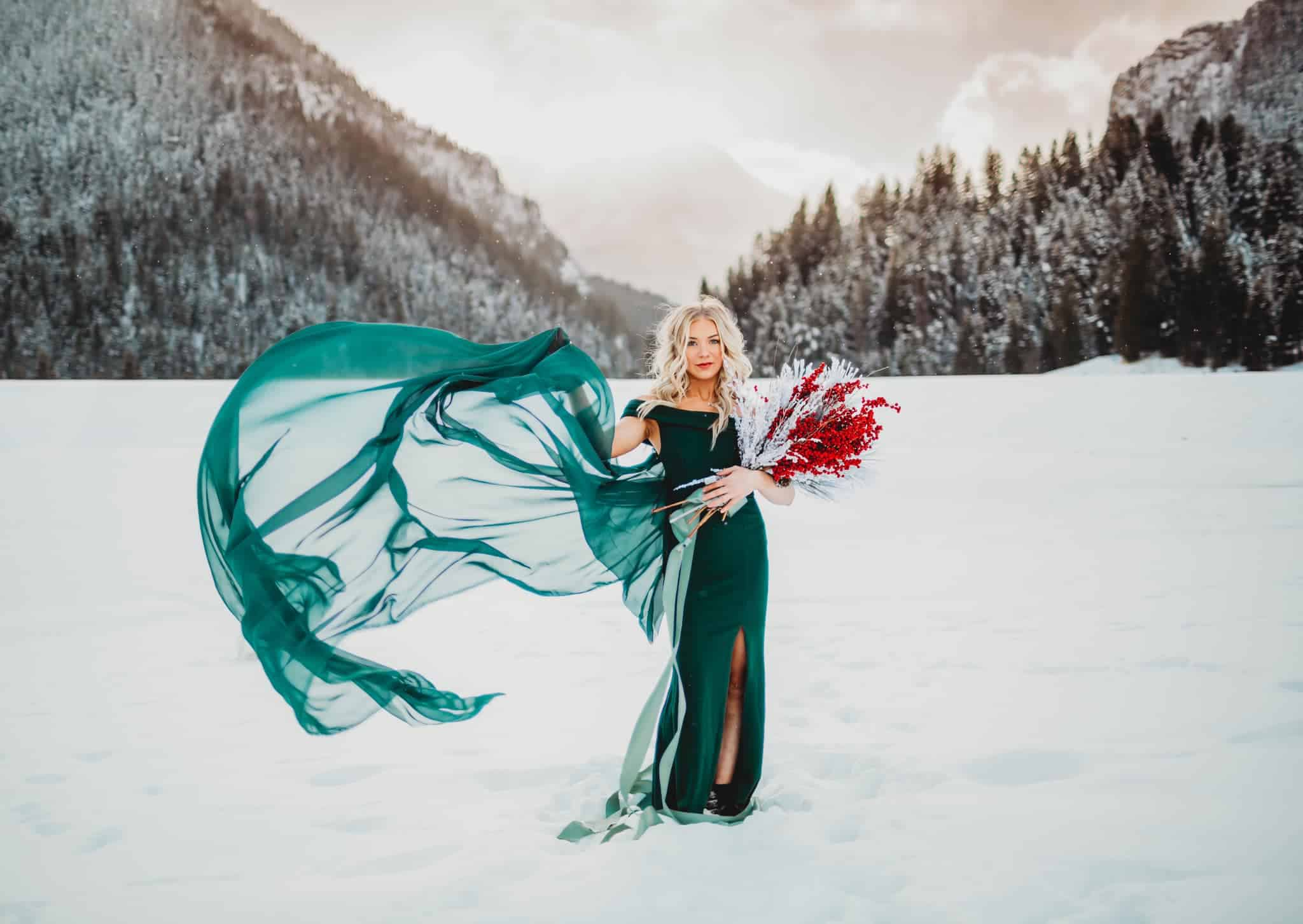 bridal portrait of a bride in the snow, wearing a green dress