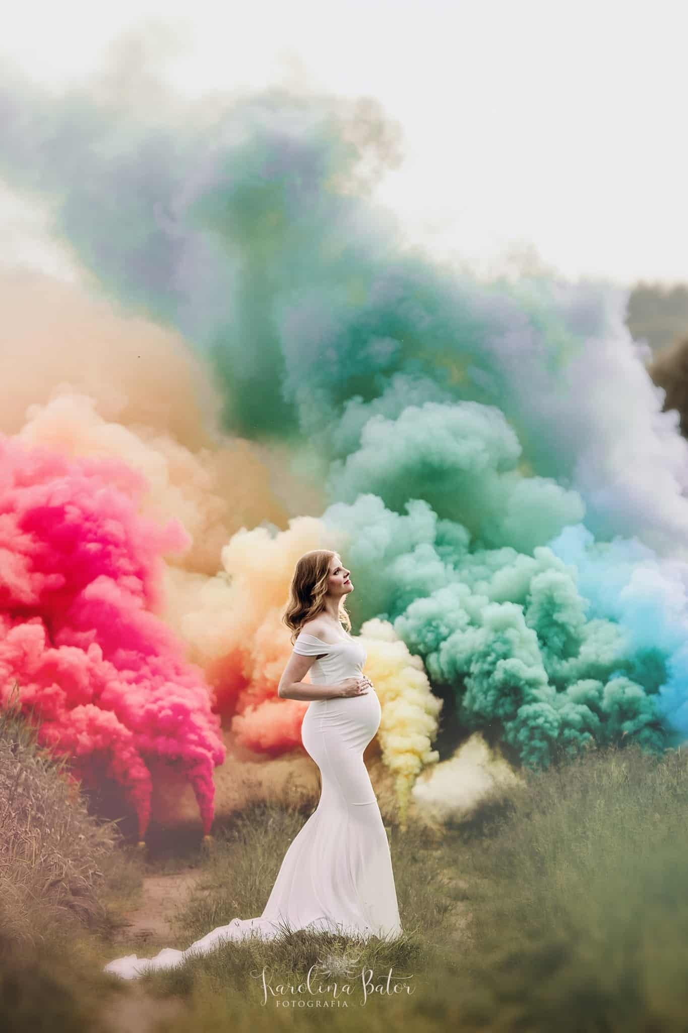 a prägnant woman in a white dress surrounded by colorful smoke bombs