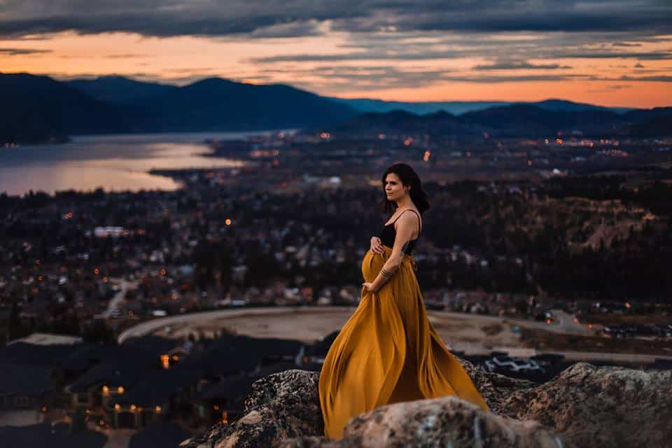 W pregnant woman standing on a cliff with a beautiful dress