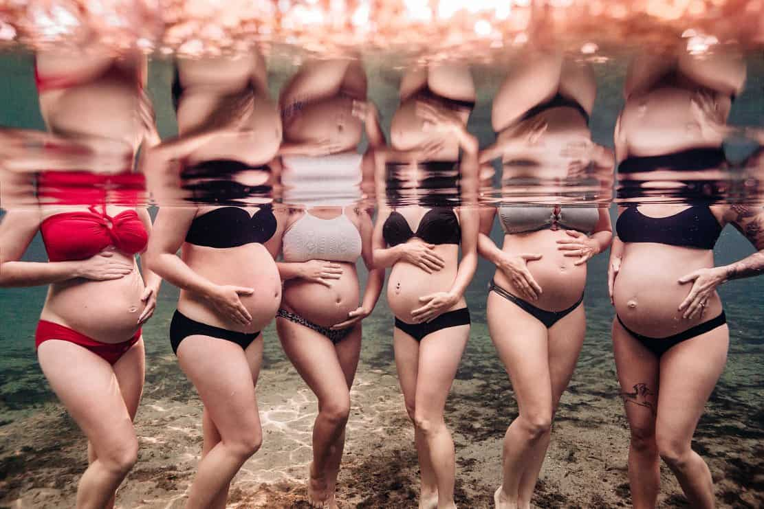A group of pregnant women holding their bellies underwater
