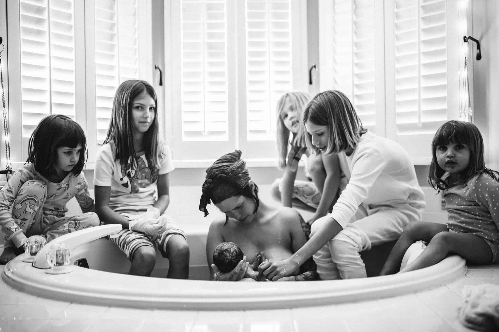 5 sisters are watching their mother give birth in a home water birth