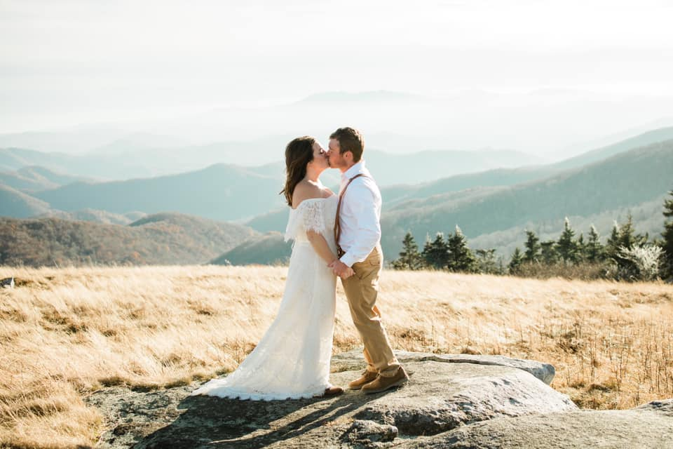A wedding couple is kissing each other in the Roan Mountains.