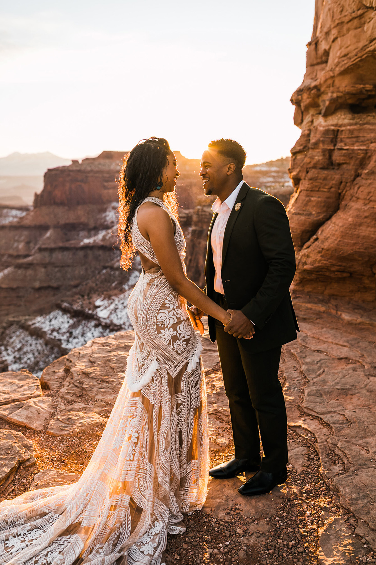 Wedding couples holding hands and looking at each other at sunrise at dead horse point