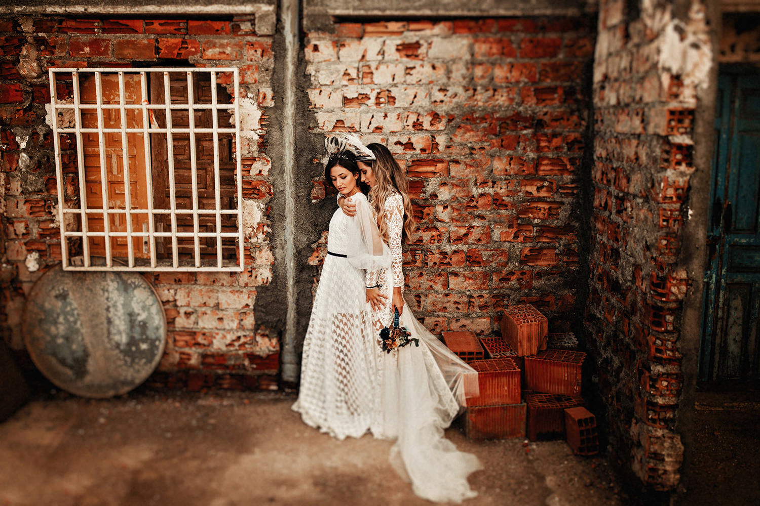 A wedding couple is holding each other and is standing in front of a brick wall, featured at the elopement checklist post.
