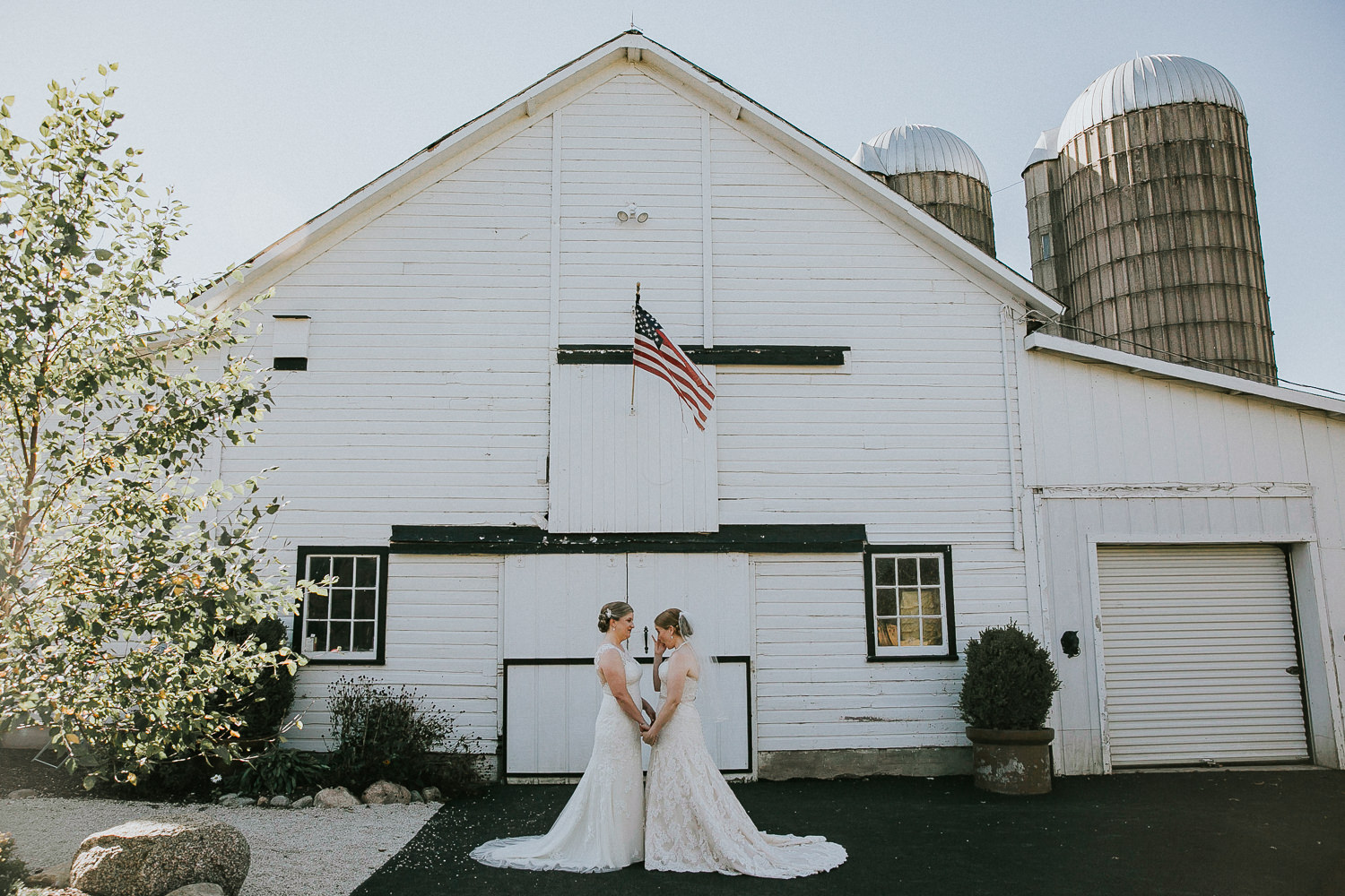 A wedding couple is standing in front of the Heritage Prairie Farm in Ohio.