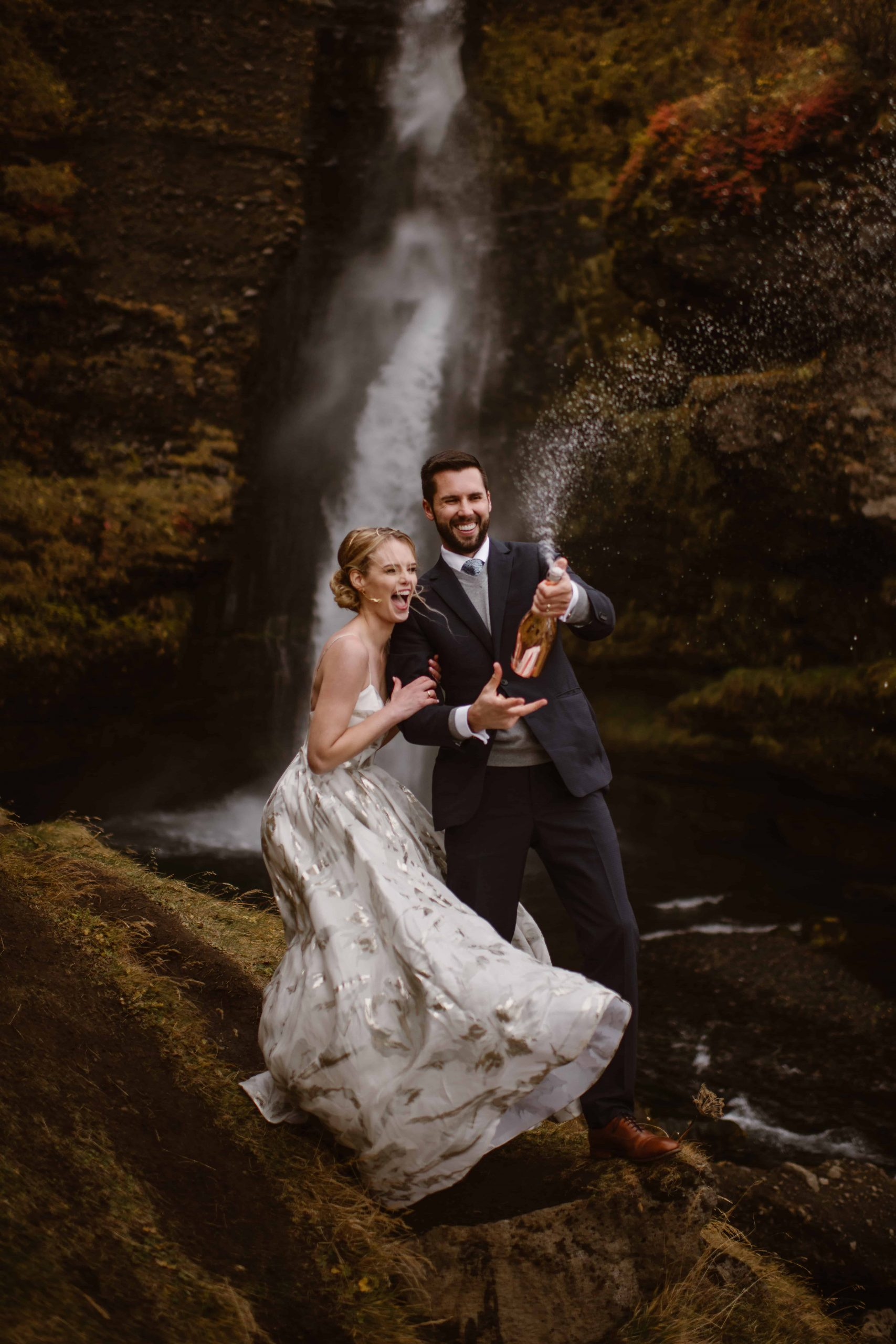 A wedding couple is popping a bottle of champaign open.