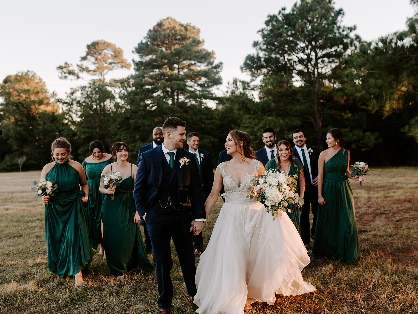 A wedding couple is standing on a meadow in front of their bridesmaids and groomsmen.