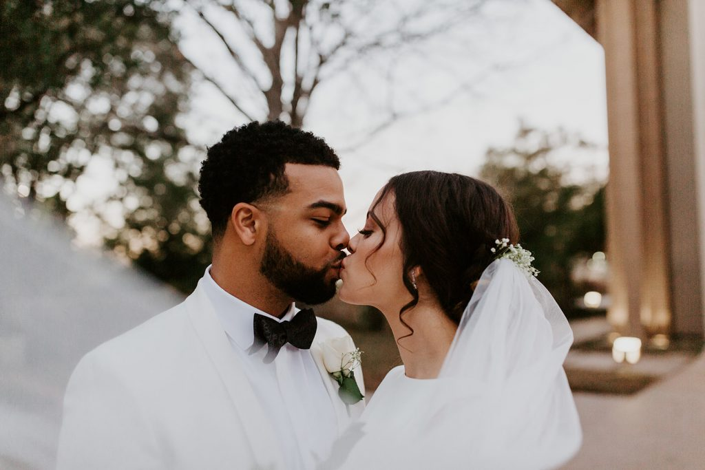 A wedding couple is kissing each other in Texas, photographed by Meme Urbane.
