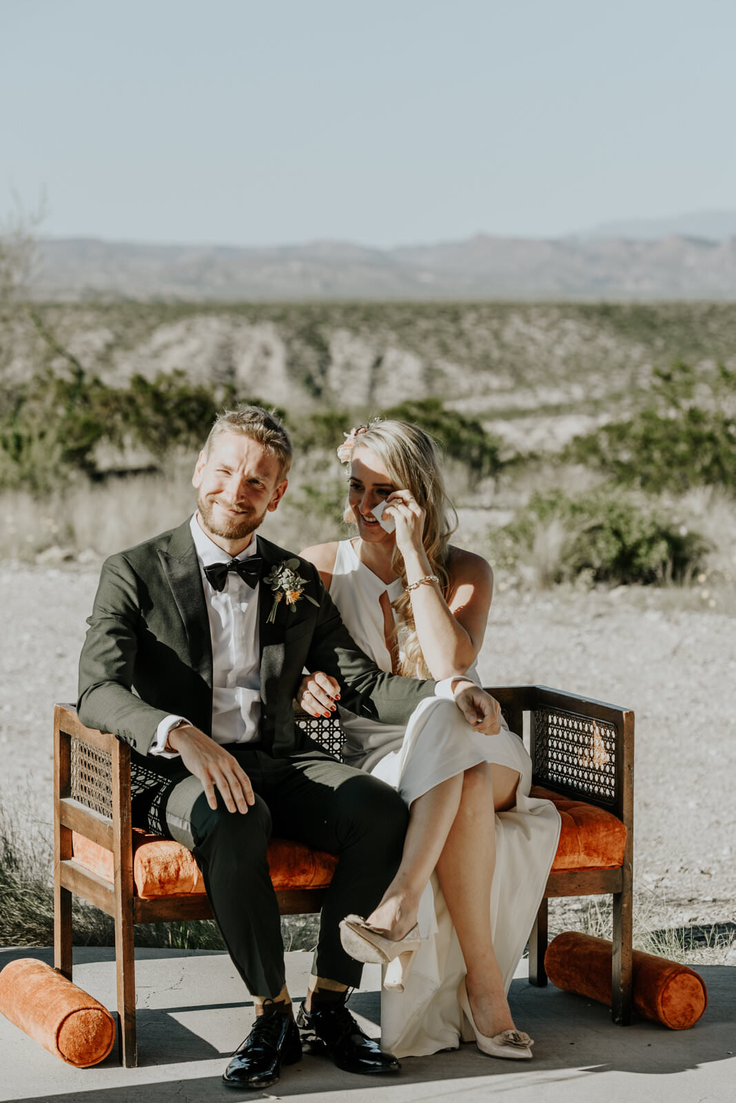A wedding couple is sitting on a chair.