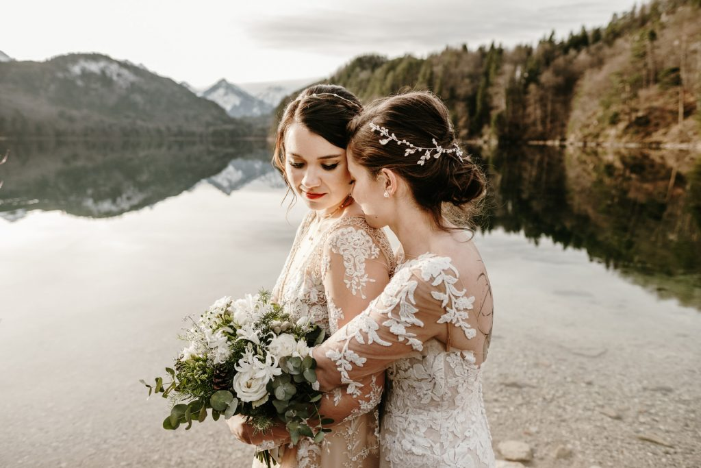 A wedding couple is holding each other and standing in front of a lake.