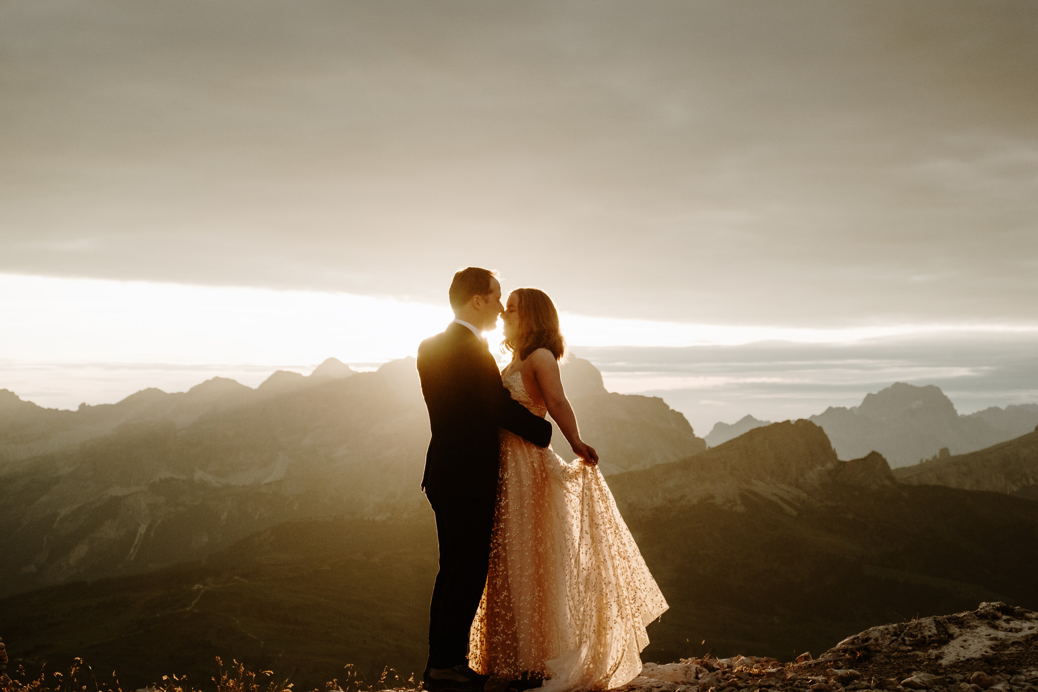 A wedding couple is holding each other and standing on top of the mountain.
