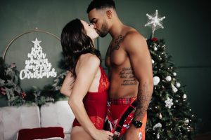 Christmas Boudoir Ideas for couples in front of a Christmas tree.