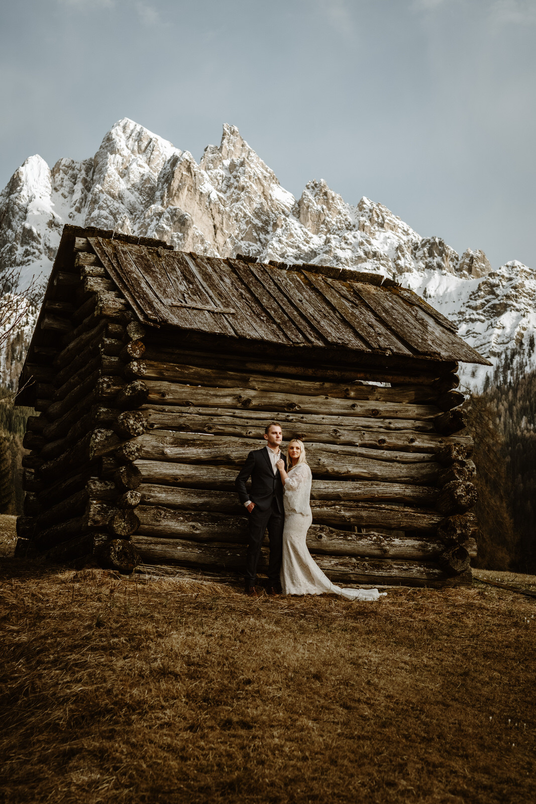 A wedding couple is standing in front of a mountain hut.