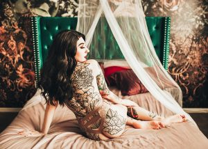 Boudoir Ideas for woman sitting on bed showcasing her back tattoos.