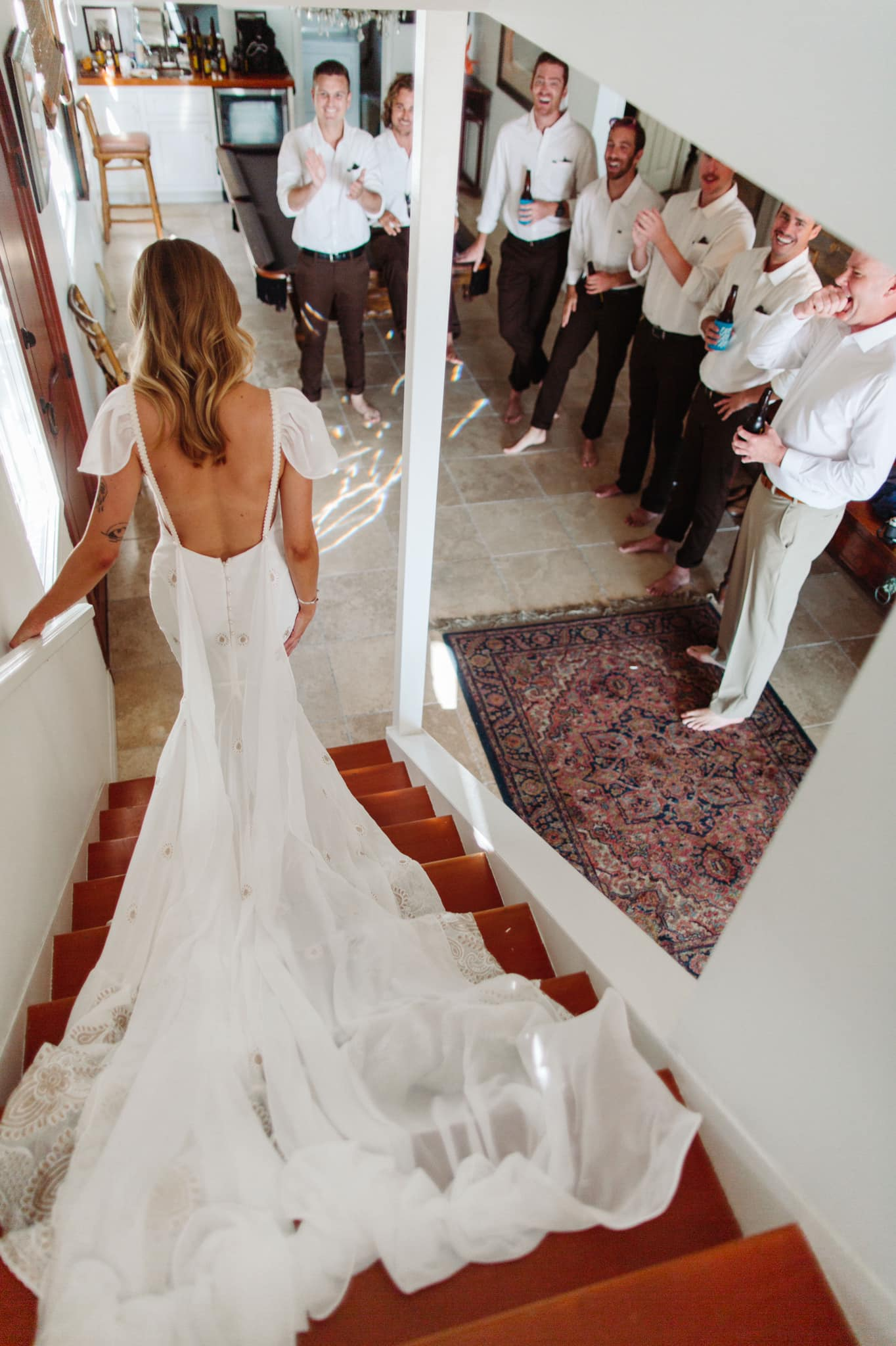 a bride walks down the stairs and the best men are amazed