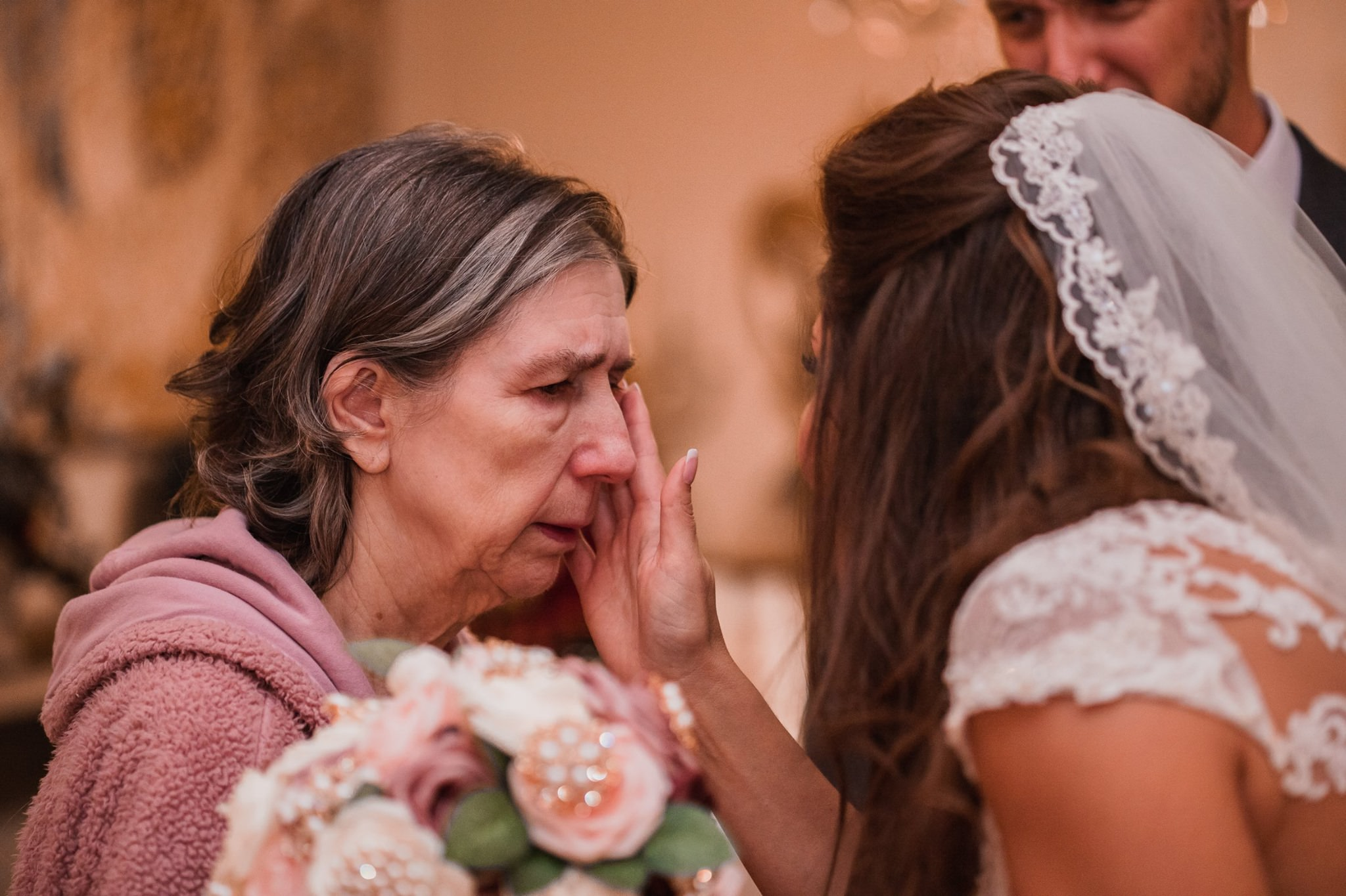 the bride wipes the tears off from her mother's face