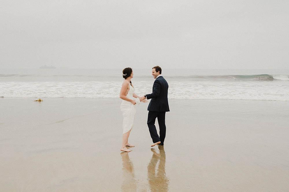 A wedding couple walking barefoot in the sand on coronado island