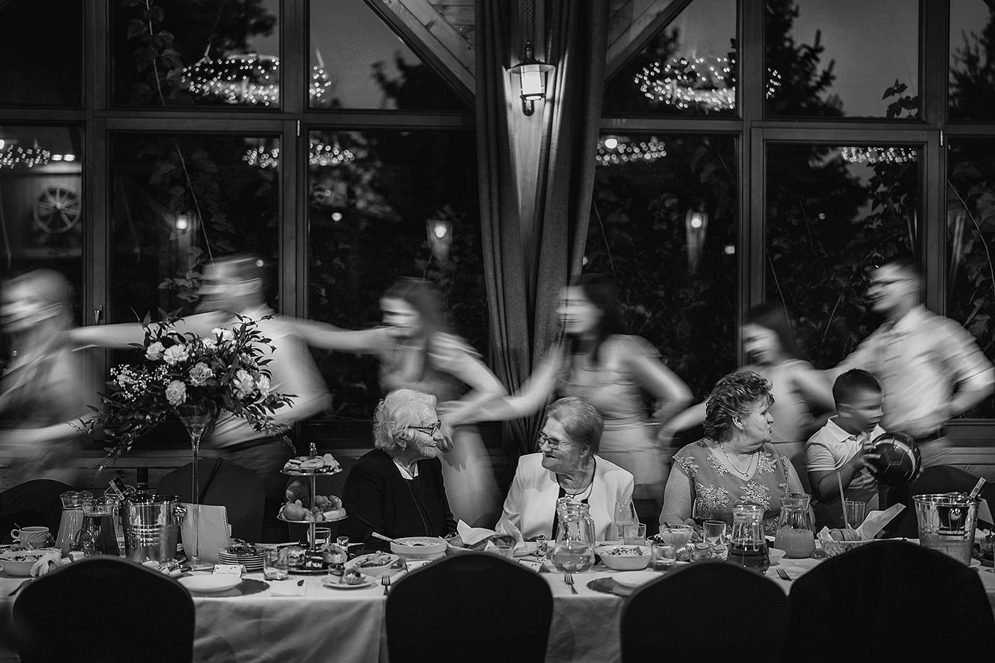 two grandmothers sit a table while the wedding guests are dancing around them