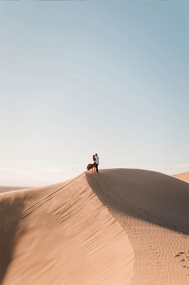A Couple standing on a sand dune at Glamis Sand Dunes