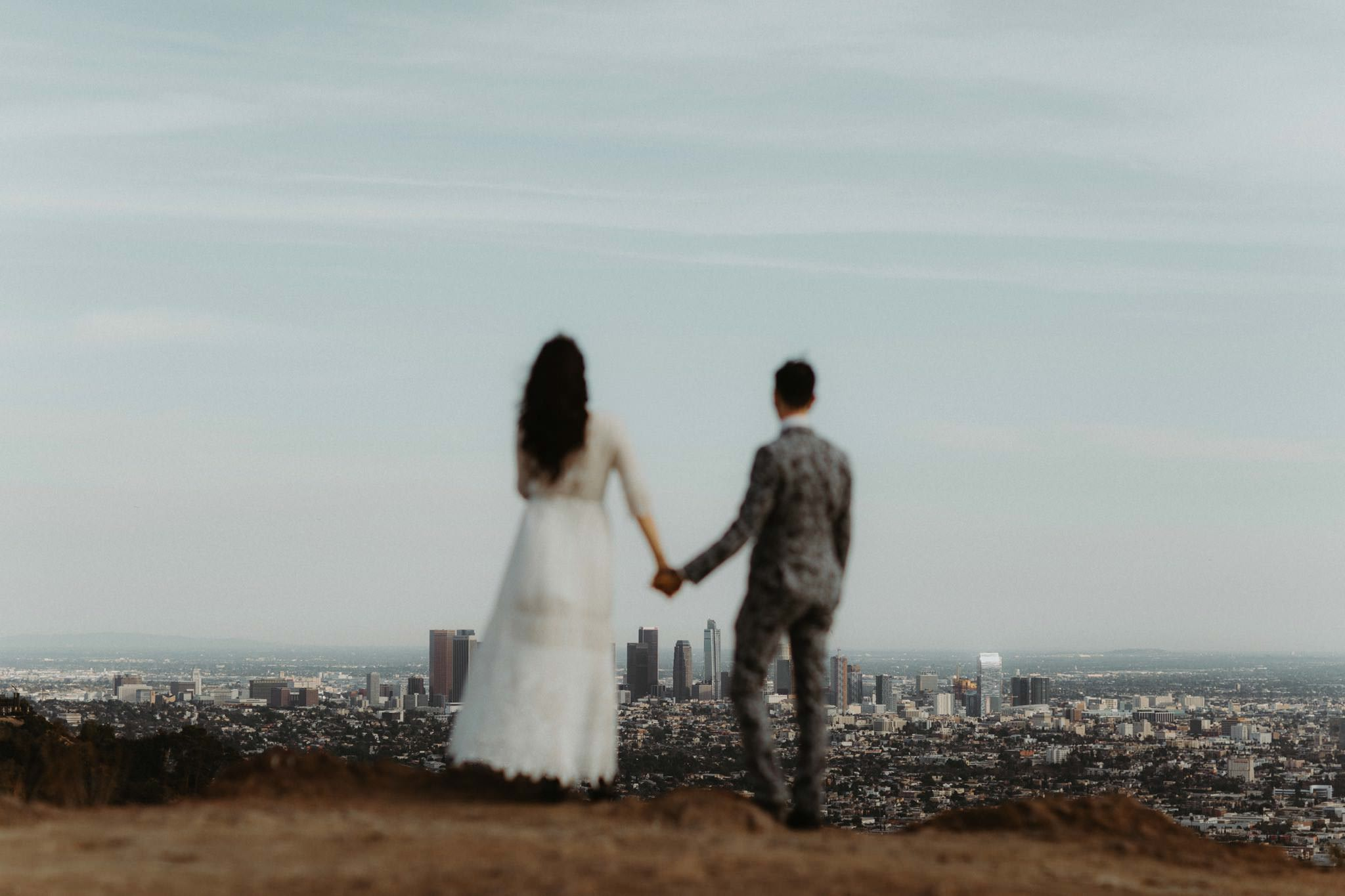 Wedding couple at Griffith State Park looking down at LA
