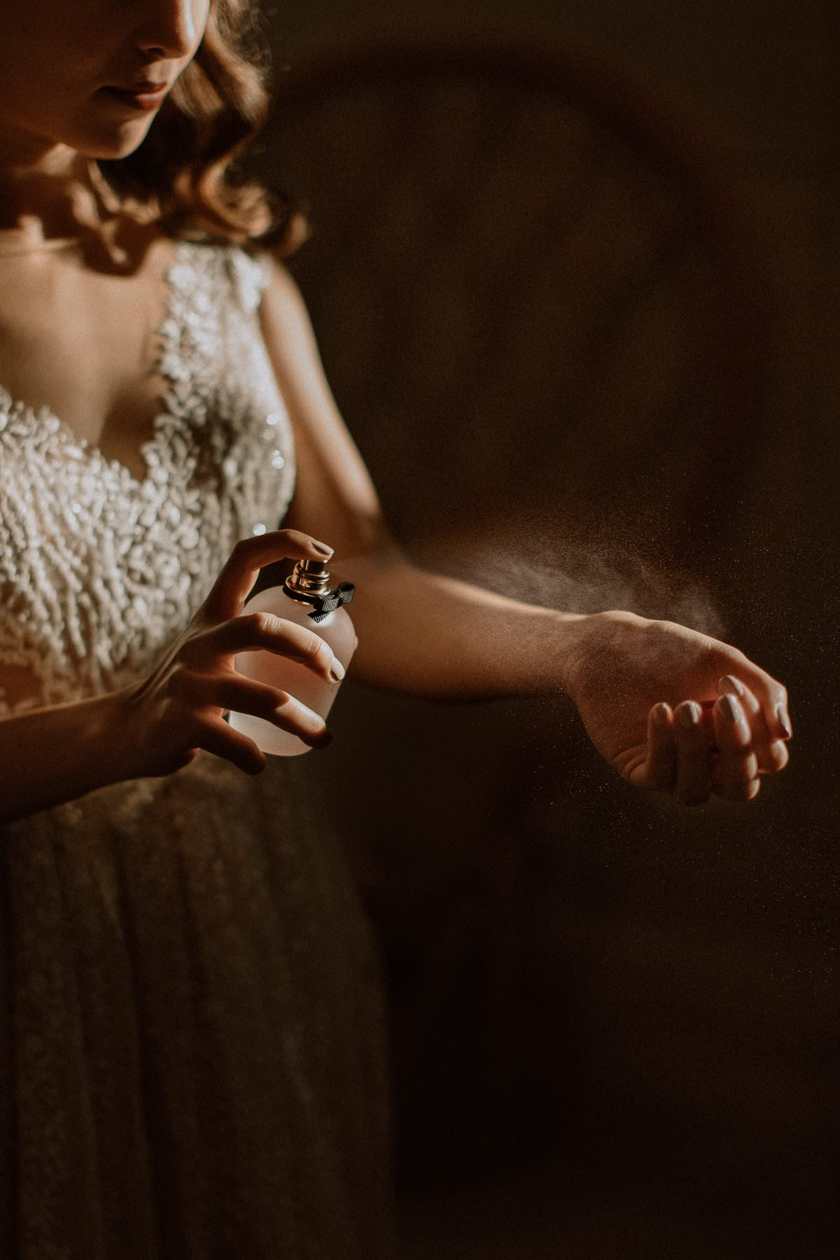 a bride sprays perfume on her hand