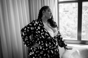 Black Boudoir photographer example of work of a plus size client near a window.