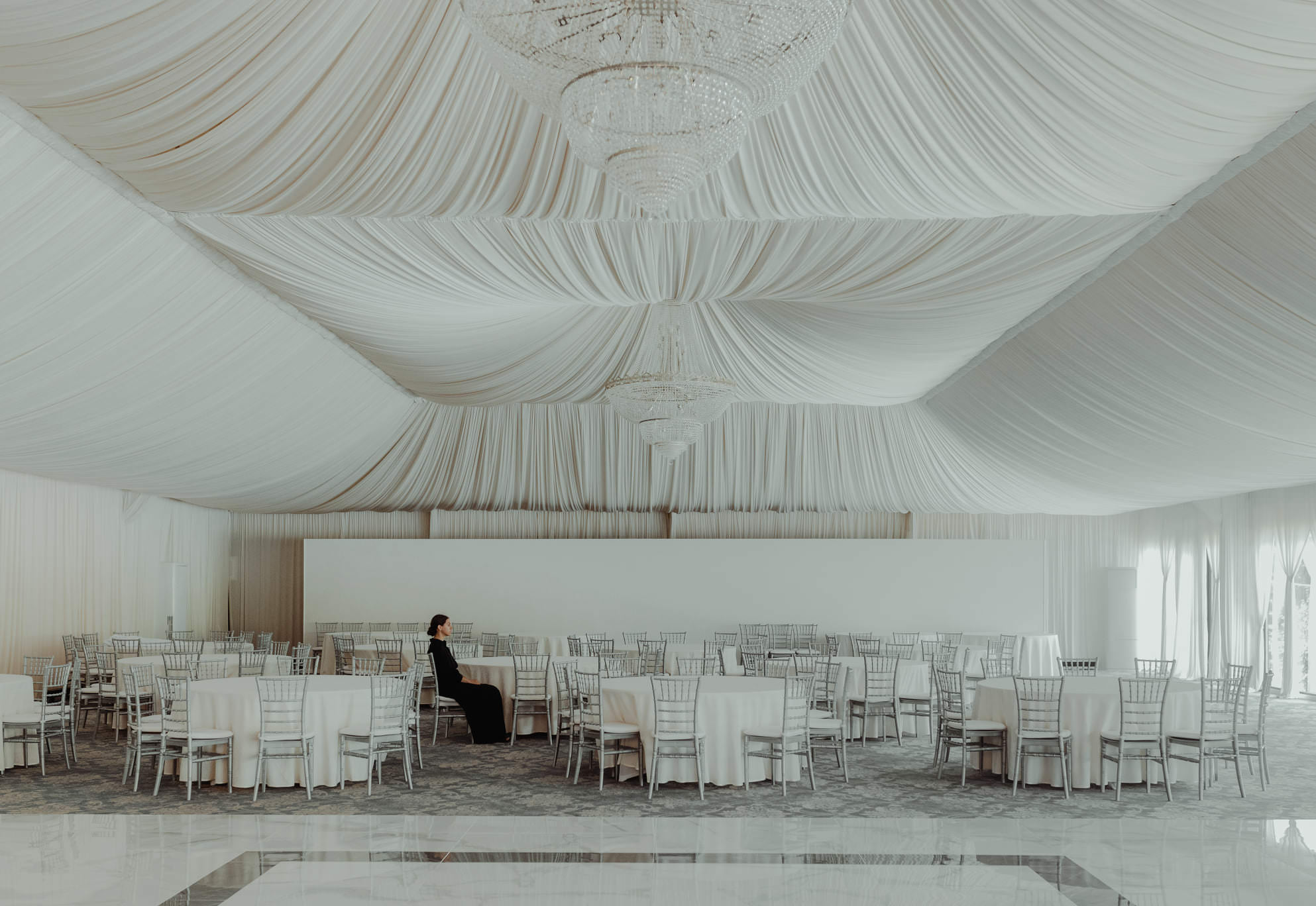 a woman sits alone in an empty wedding venue