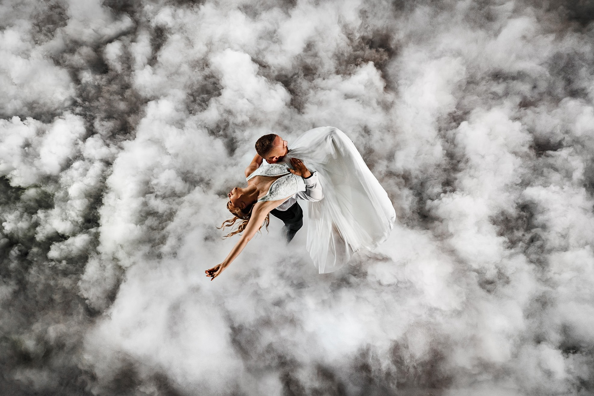 a bride and a groom are dancing their first dance and the dancefloor is coverd in fog