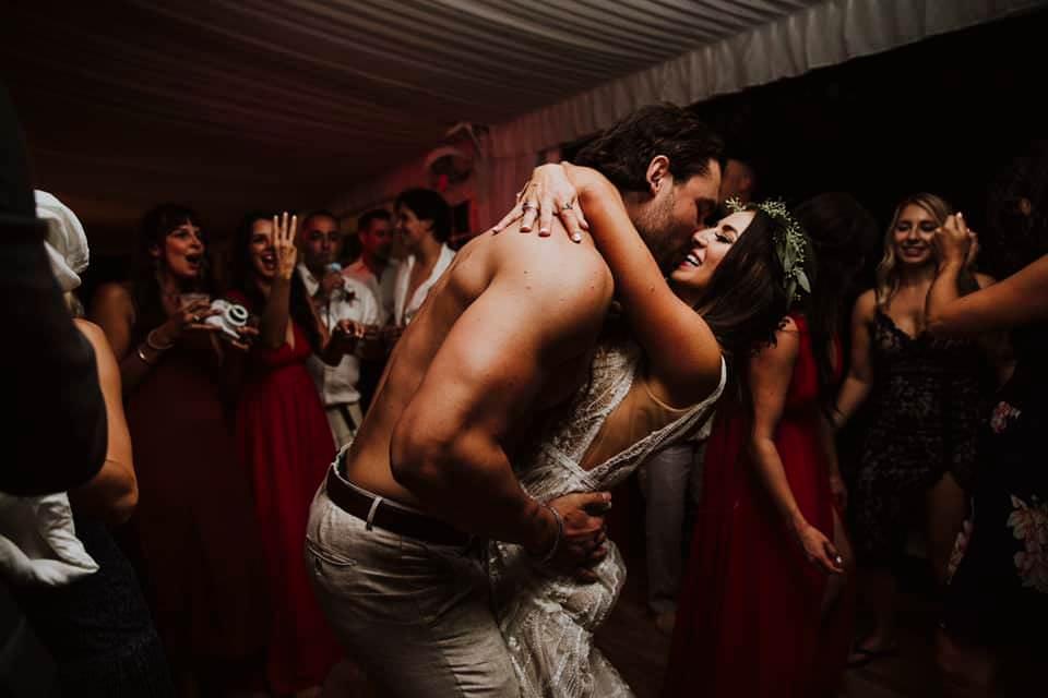 a topless groom hugs his bride on the dancefloor
