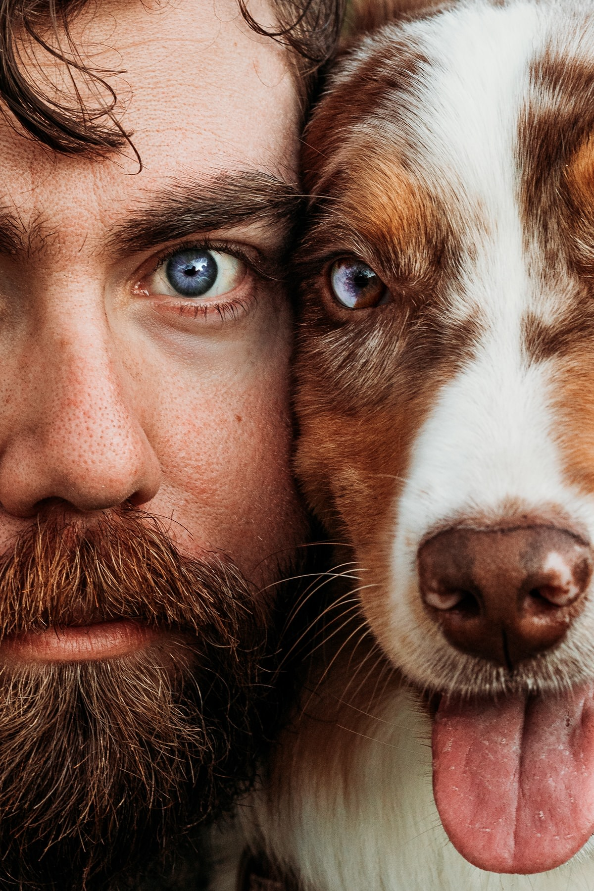 a man and a dog look into the camera cheek by cheek