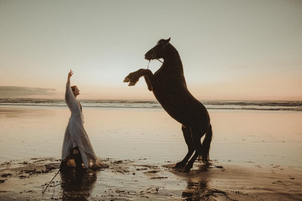 a woman is training her horse on the beach