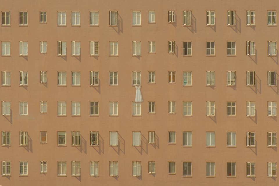 a detail shot of a bride's wedding dress hanging outside a house facade full of windows