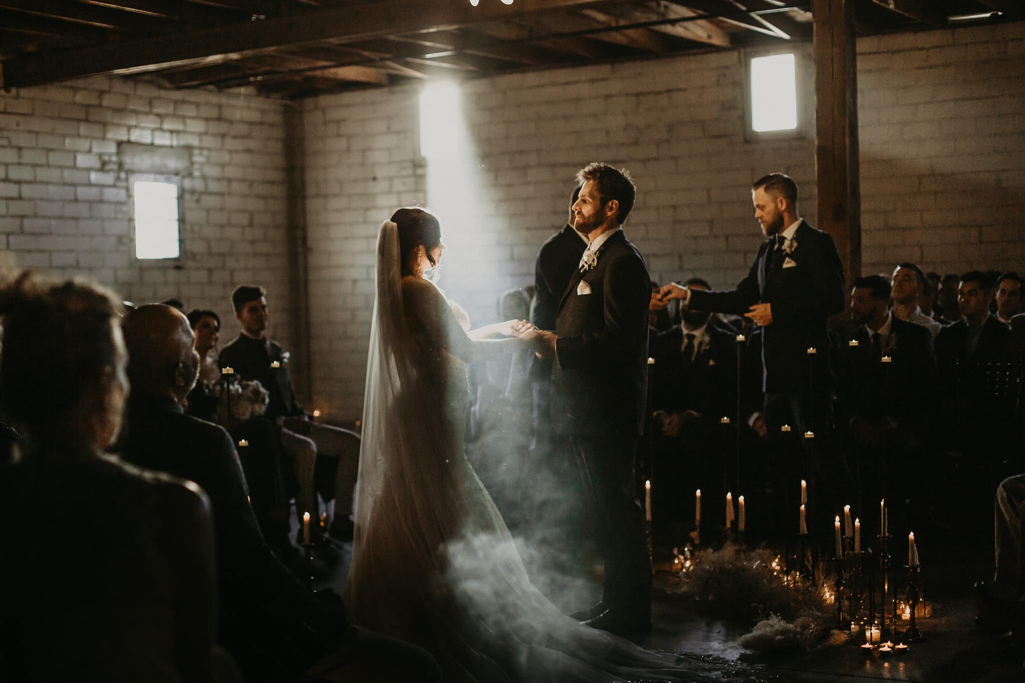 a wedding ceremony in a very dark room where the sunlight from outside shines on the wedding couple