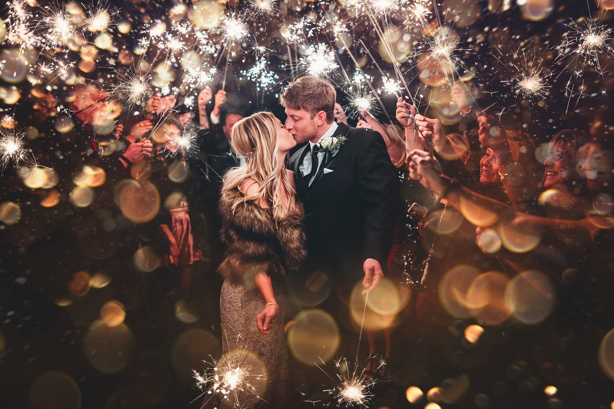 a wedding couple kissing while their sparkler exit