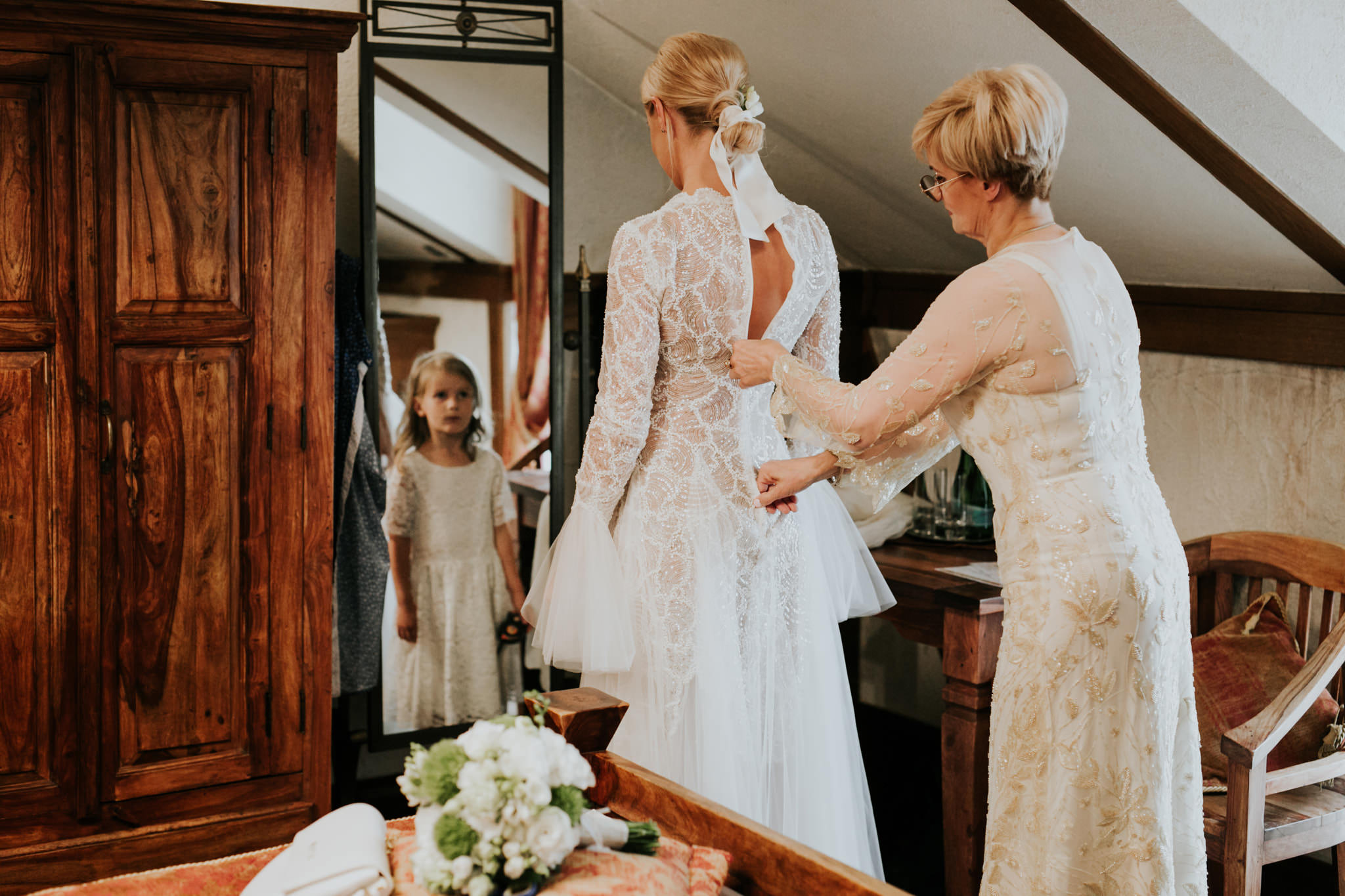 the bride's mother helps the bride to get into her wedding dress, while the bride's daughter is flashed by the beauty of her mother